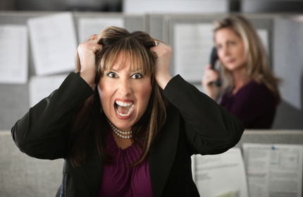 Frustrated female office worker in a cubicle pulls her hair